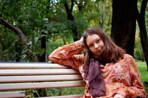 Kuvassa nuori nainen istuu puistonpenkillä.