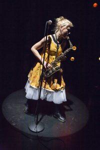 Kädettömät – Käsist seotud Lahden kaupunginteatterissa. Kuvassa näyttelijä Anna Lipponen soittaa saksofonia.