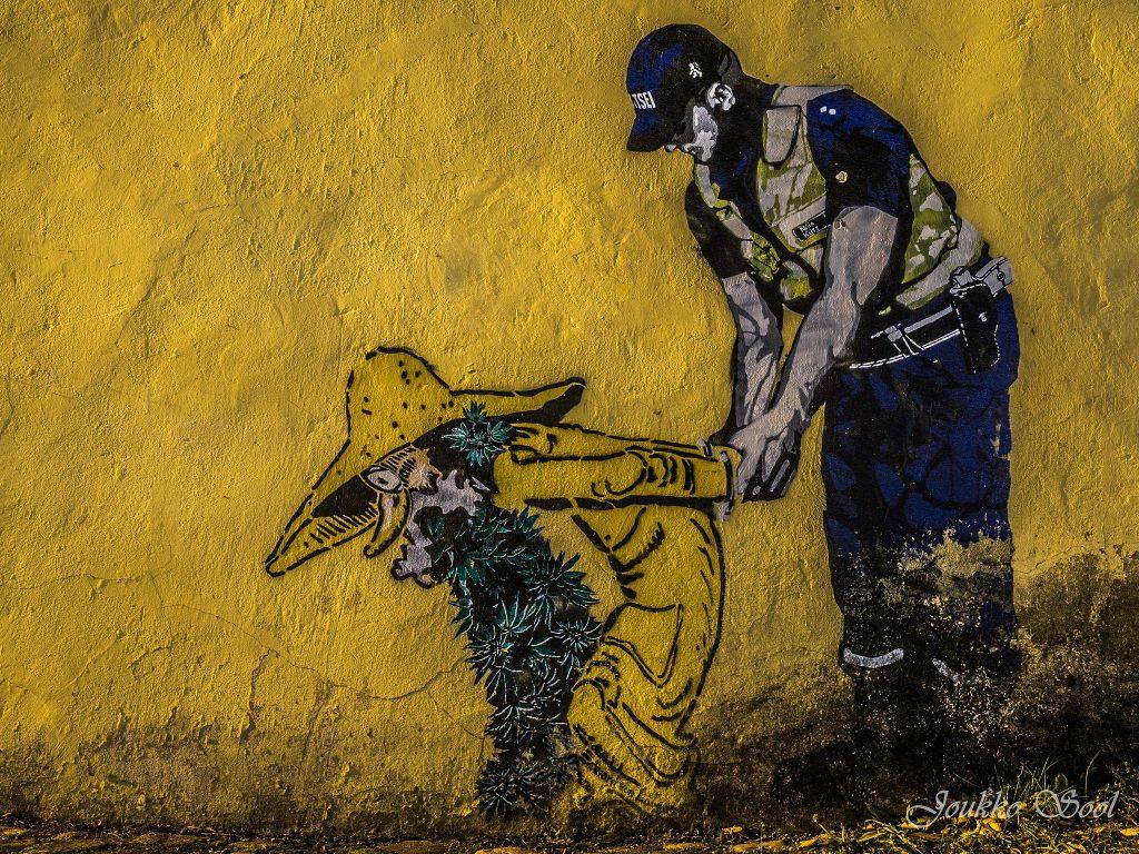 Keltainen seinä, jossa Edward von Lõngusin katutaideteos, joka kuvaa tontun näköisen hahmon pidättämistä