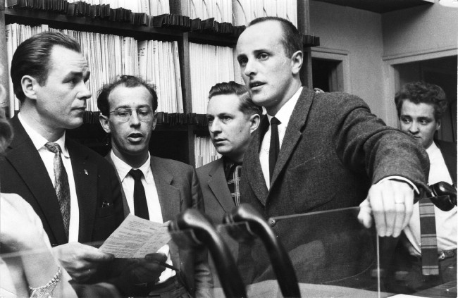 Mustavalkoinen kuva, jossa miehiä puvut päällä 50-luvulla.