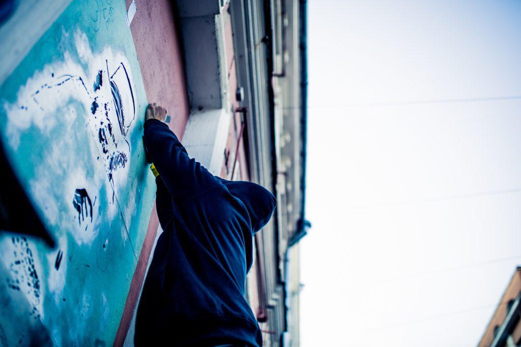 Katutaiteilija työskentelemässä sinisen teoksen kanssa.