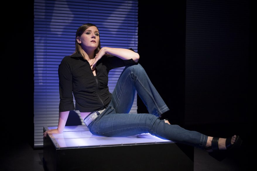 Nuori naisnäyttelijä istuu keskellä kuvaa vaalepohjaisella alustalla ja pitää kättään leuan alla ylväästi. Tausta on pimeä, yksi sinertävä kaistale valoa suoraan näyttelijän takana.
