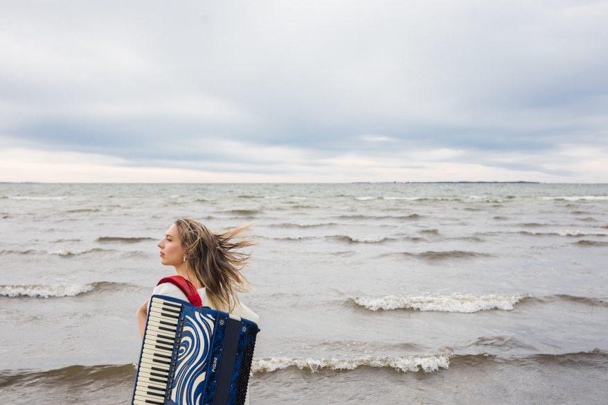 Tuulikki tuulisella rannalla harmonikan kanssa.