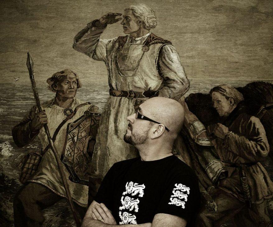 Kalju mies seisoo keskellä kuvaa, päällään musta t-paita. Taustalla iso maalaus, jota hän katsoo sivuttain.