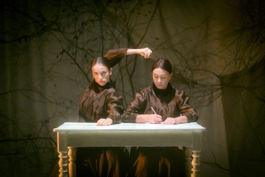 Kaksi naista lavalla, yhden pöydän ääressä, kummallakin ruskea mekko.