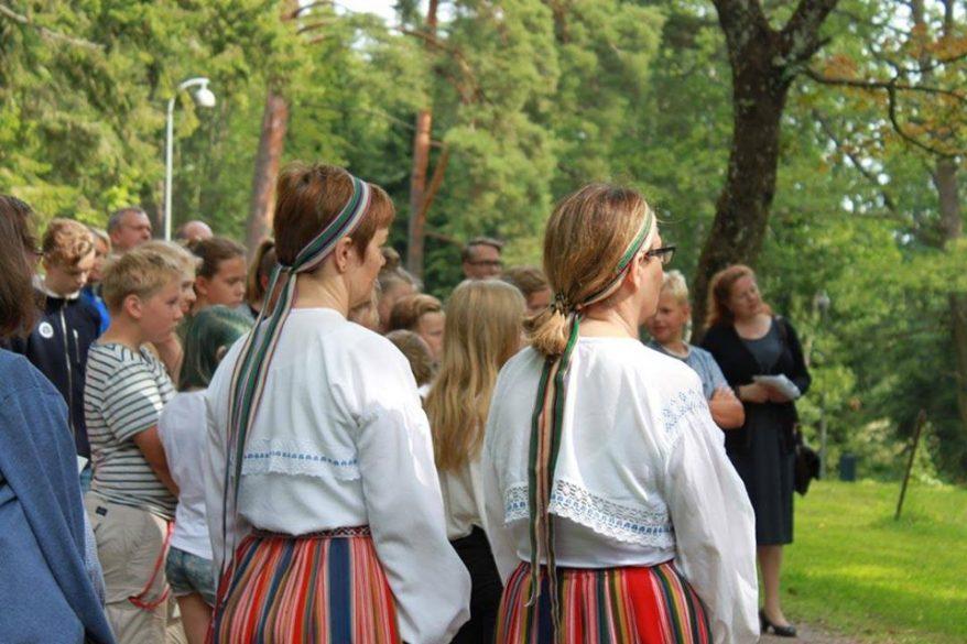 Kaksi kansallispukuihin pukeutunutta naista seisoo ja laulaa Seurasaaren vehreässä ympäristössä.