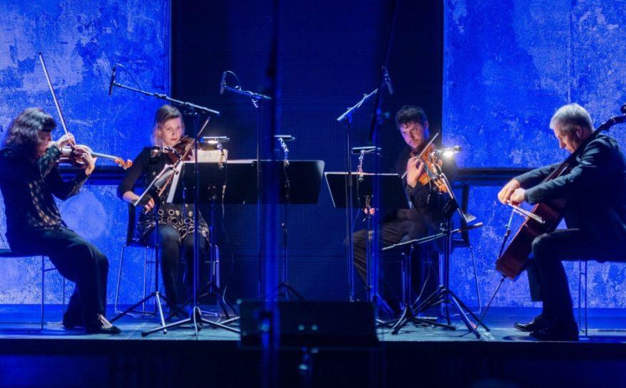 Neljä henkilöä soittaa klassisen musiikin instrumentteja lavalla.