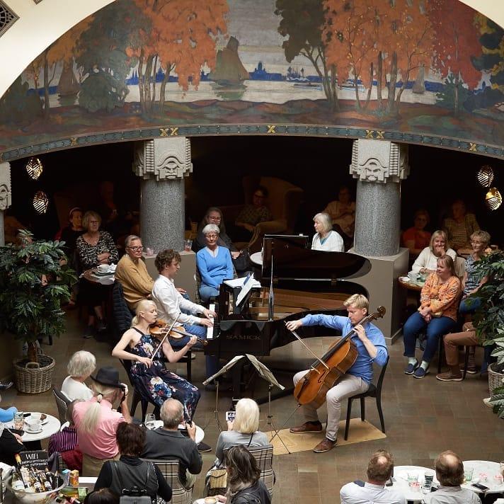Pianisti, viulisti ja sellisti esiintyvät kuvan keskellä, ympärillä ihmisiä katsomassa.