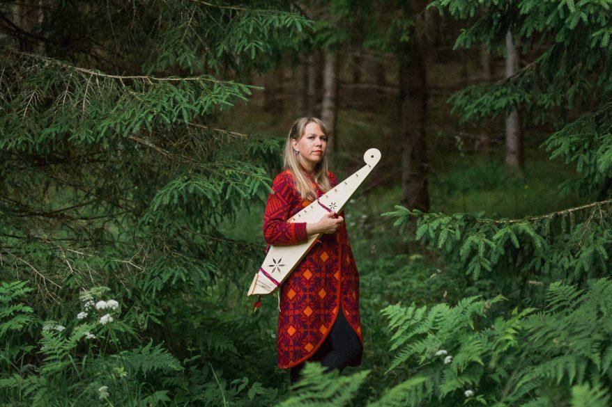 Muusikko Mari Kalkun metsässä kanteleensa kanssa.